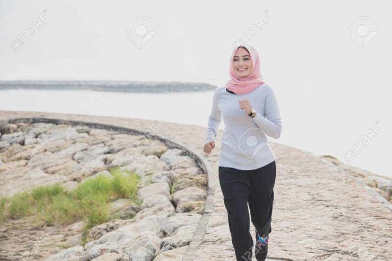 portrait of asian sporty woman wearing hijab jogging at the jogging track